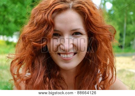 Beautiful young redhead woman smiling happily