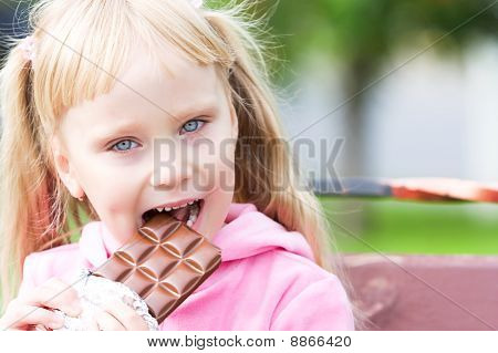 Happy little girl with a chocolate