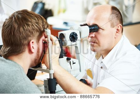 Male optometrist optician doctor examines eyesight of female patient in eye ophthalmological clinic
