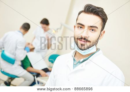 Portrait of male asian dentist wearing lab coat while sitting in clinic