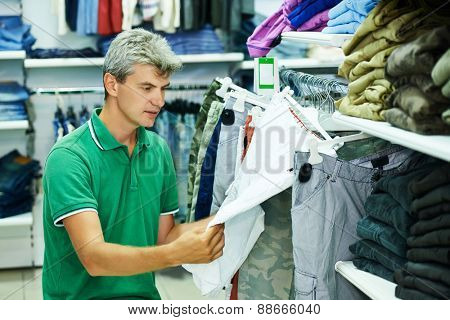 man choosing trousers during shopping at garments clothing shop