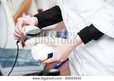 pharmaceutical female worker scanning barcode of medicine drug in a pharmacy drugstore