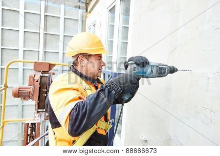 worker builder making construction for ventilation facade on a building with screwdriver drill