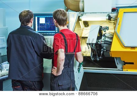 two industrial workers at cnc turning machine center in tool manufacture workshop