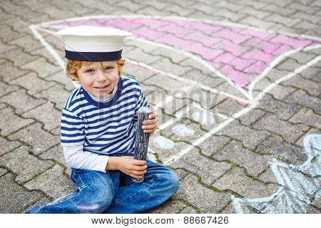 Little Kid Boy Having Fun With Ship Picture Drawing With Chalk