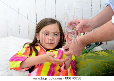 A Little Girl In Bed Taking Tablet