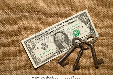 Us Dollar Banknotes And Keys On An Old Cloth