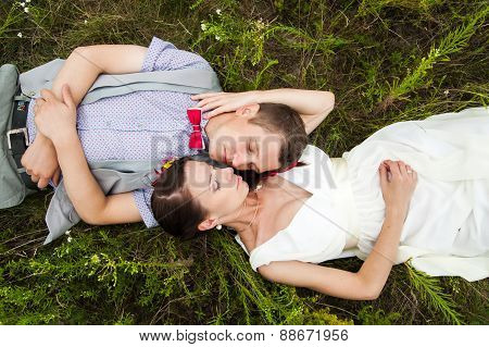 Wedding Couple In Love Lying In Green Grass In Summer Meadow