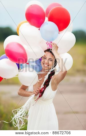 Happy Young Woman Holding In Hands Colorful Latex Balloons Outdoors