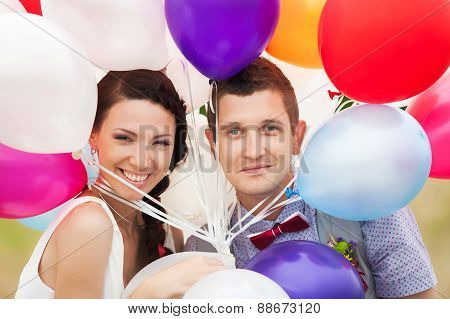 Man And Woman Holding In Hands Many Colorful Latex Balloons