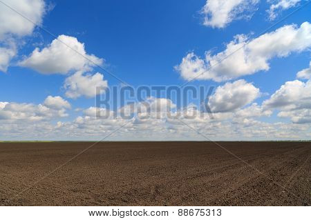 landscape with a farm field under sky with clouds