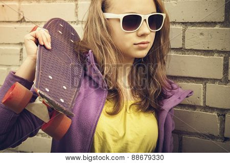 Blond Teenage Girl In Sunglasses Holds Skateboard