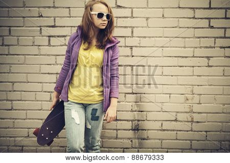 Teenage Girl In Jeans And Sunglasses Holds Skateboard
