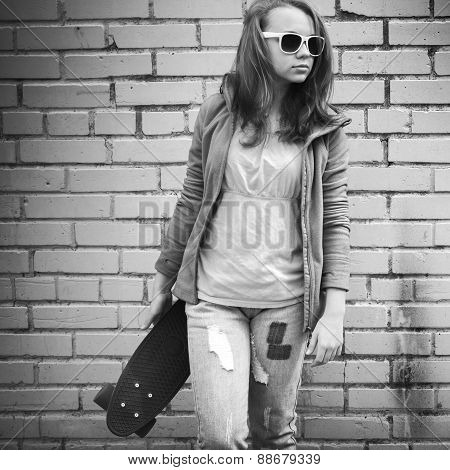 Blond Teenage Girl In Jeans And Sunglasses Holds Skateboard