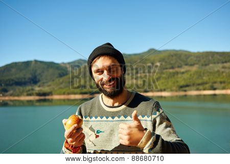 Beautiful Bearded Man Hiker Smiling Happy  Eating An Apple During Break And Showing Thumbs Up.