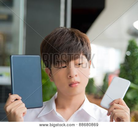 Asian male decide if tablet or smartphone  is better