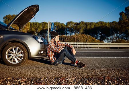 Young Brutal Man Sits Near Car Talking On Cell Phone Because His Auto Broken Down. Thoughtful 20S