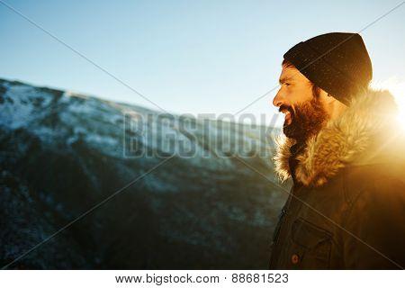 Hiker On Top Of The Mountain Enjoying Sunrise. Happy Smiling Bearded  Traveler