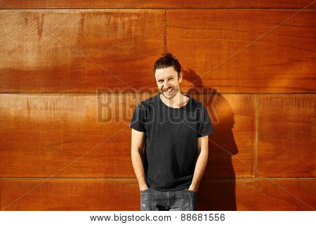 Hipster On City Wall Smiling Happy After Walking Vacation Looking At Camera. Male Model Enjoying Sun