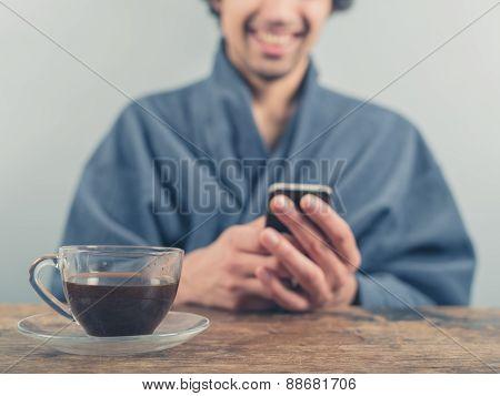 Man In Bathrobe Using Smart Phone And Drinking Coffee