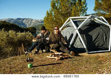 Couple Camping Drinking Coffee Near Tent Smiling Happy Outdoors In Mountain Forest Enjoying Sun