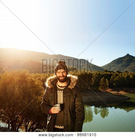 Strong Hiker Standing On The Mountain Near Lake In Background And Resting With Hot Coffee.