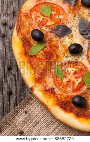 Italian pizza margherita with tomatoes, olives and basil close u