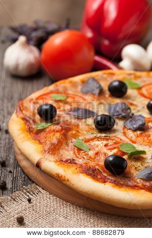 Traditional pizza margherita with tomatoes, olive oil and basil