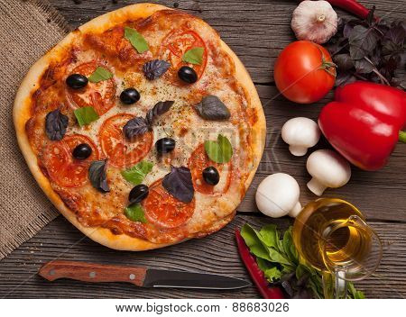 Traditional pizza margherita with tomatoes, pepper, olives and b