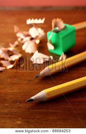 Two sharpened pencils and one in a pencil sharpener