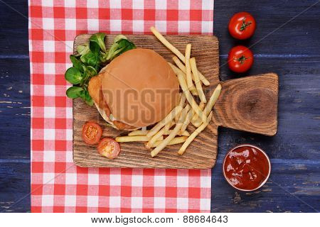 Hamburger, french fries and sauce on wooden table top view