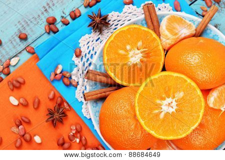 Orange tangerines, peanuts and cinnamon sticks on blue wooden table top view