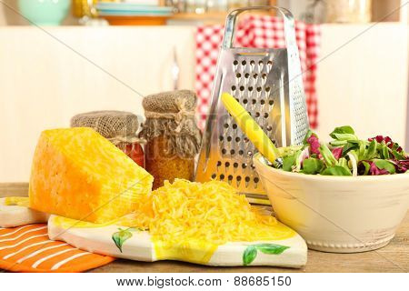 Grated cheese on wooden table in kitchen, closeup
