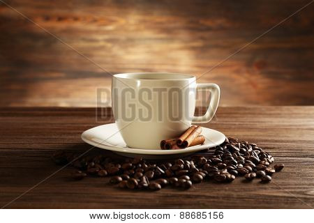 Cup of coffee with grains and cinnamon sticks on wooden background