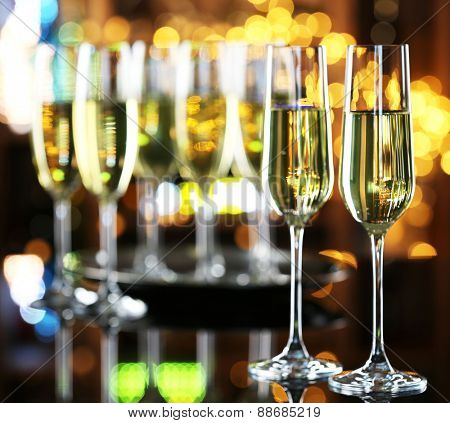 Glasses of champagne on bar background
