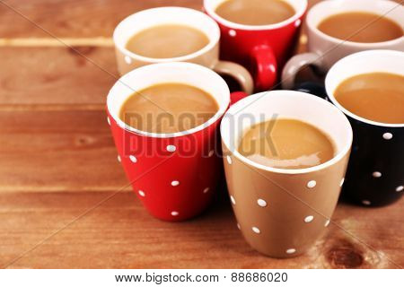 Cups of cappuccino on wooden table, closeup
