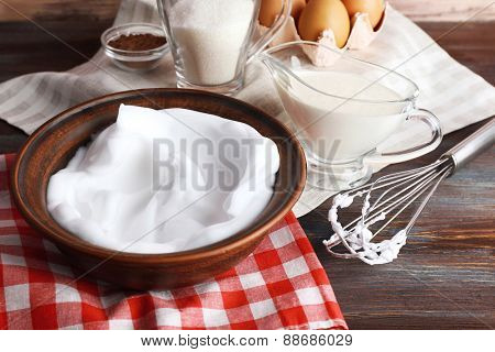 Whipped egg whites and other ingredients for cream on wooden table, closeup
