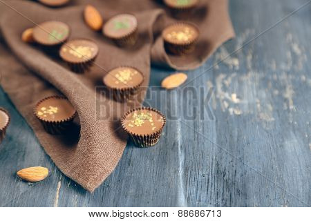 Tasty chocolate candies on napkin, on wooden table