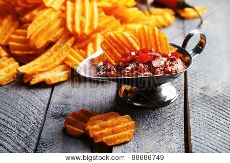 Delicious potato chips with sauce on wooden table close-up