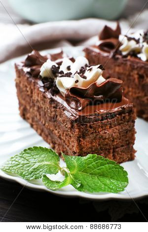 Tasty pieces of chocolate cake with mint on wooden table background