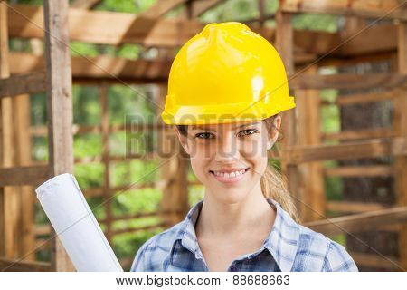 Portrait of confident female architect wearing yellow hardhat in wooden cabin at construction site