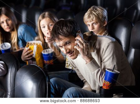 Annoyed family looking at man using mobilephone in cinema theater