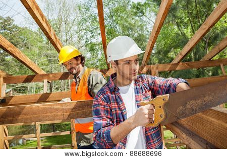 Male construction worker cutting wood with handsaw while colleague in background at site