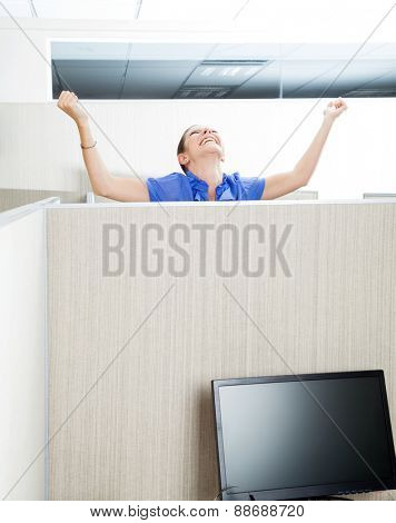 Female customer service representative celebrating success in cubicle