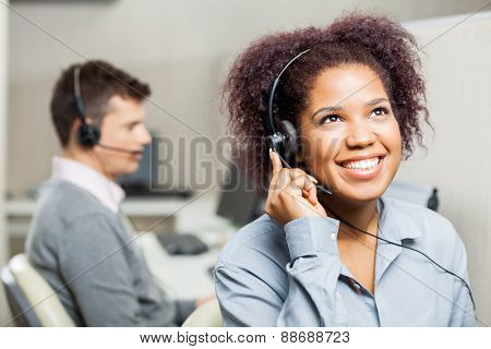 Happy female call center agent using headset with male colleague in office