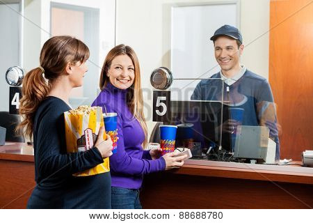 Happy women holding snacks while buying movie tickets from male seller at box office