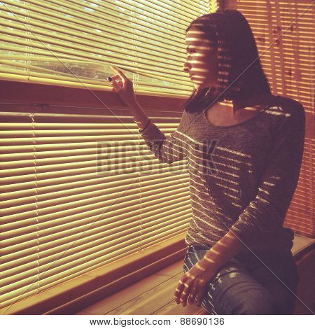 Attractive girl looks out blinds