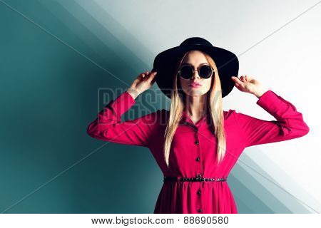 Expressive young model with hat and sunglasses on wall background