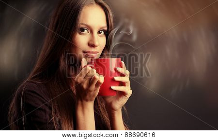 Beautiful young woman with cup of coffee on dark background
