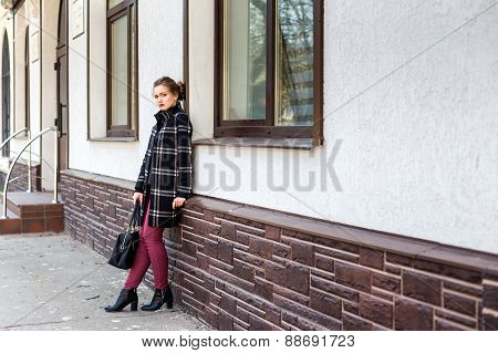 Young Beautiful Woman With A Fashionable Bag Is Standing On The Street